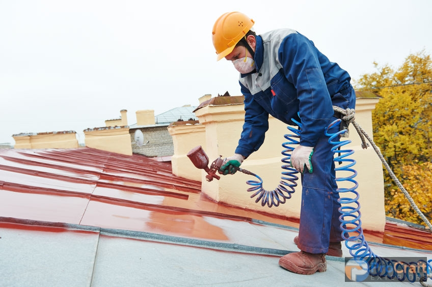 Builder Spraying A Roof Coating on a Metal Roof